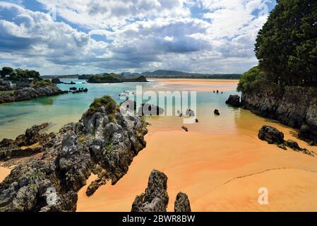 Rock formations and clean wet sand at beautiful beach during low tide - Stock Photo