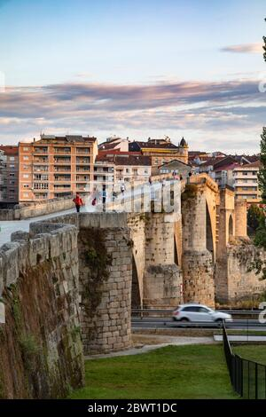 People crossing the Roman bridge early in the morning, Ourense, Galicia, Spain. Stock Photo