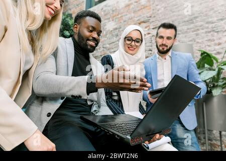 Team of multiethnical diverse business people, two men and two women, standing in modern office, discussing and working together, using laptop and