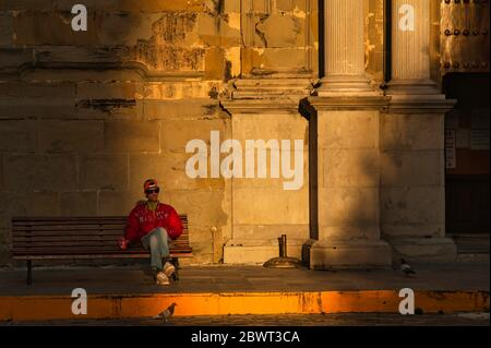 man sitting outside San Mateo Church, Iglesia de San Mateo, Old Town, Tarifa, Cadiz Province, Andalucia, Spain. - Stock Photo
