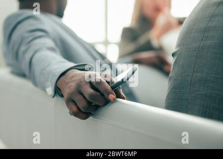 close up. casual young man sitting in the office lobby Stock Photo