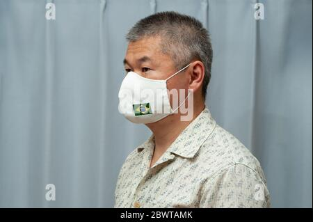 COVID-19 Pandemic - Side view portrait of middle aged Asian man wearing DIY homemade surgical face mask with Brazil flag. Coronavirus protection. - Stock Photo