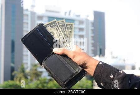 Young man hands showing dollar bills . dollar bills on corporate company background. - Stock Photo