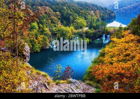 Croatia, Scenic view of lake surrounded by autumn forest in Plitvice Lakes National Park - Stock Photo