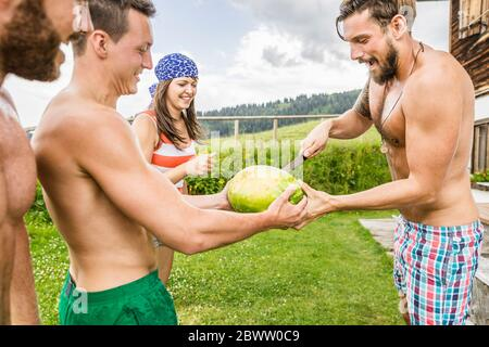 Friends sharing a watermelon on a meadow in the mountains, Achenkirch, Austria - Stock Photo