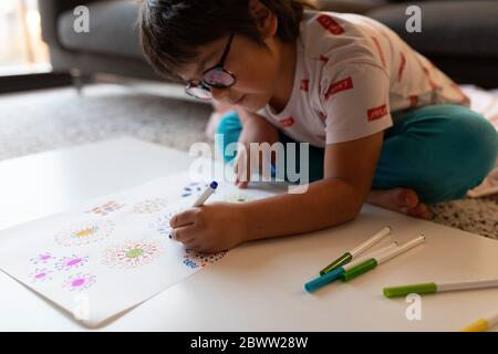 Boy sitting on the floor at home drawing flowers - Stock Photo