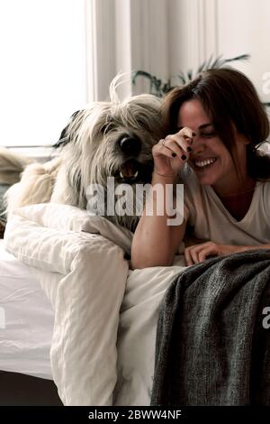 Laughing mature woman lying on bed playing with her dog