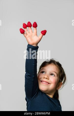 Portrait of happy girl with raspberries on her fingers - Stock Photo