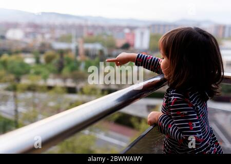 Little girl standing on balcony pointing on something - Stock Photo