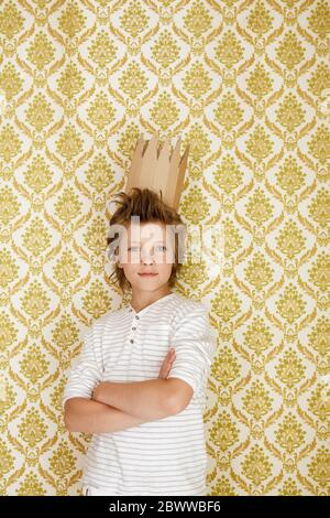 Portrait of a boy standing at a wall wearing cardboard crown - Stock Photo