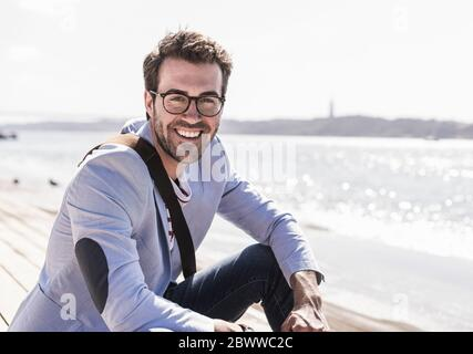 Portrait of happy young man sitting on the waterfront