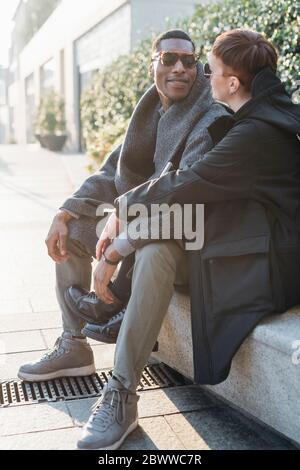 Young couple sitting on a wall in the city - Stock Photo