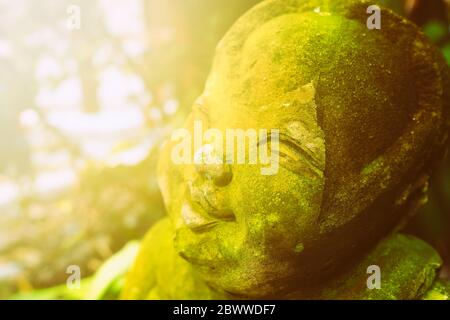 Old Cute Monk Statue be left in the Park with Light Leak Background. - Stock Photo