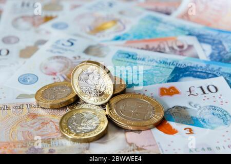 A pile of one pound £ coins British money sterling on new polymer £10 and £5 notes GBP close-up. England UK Britain - Stock Photo
