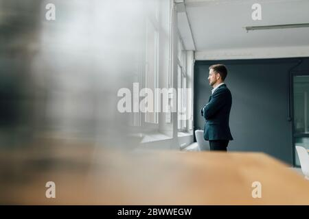 Portrait of brunette businessman looking out of window in office - Stock Photo