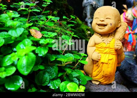 Old Cute Monk Statue be left in the Park. - Stock Photo