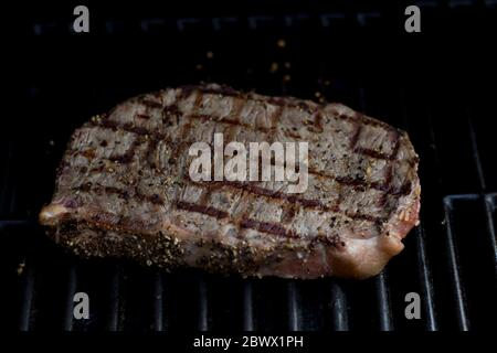 Steak BBQ close up grill marks on steak. Delicious seasoned sizzling steak on the barbeque macro view. - Stock Photo