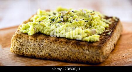 Avocado on crunchy toast, with seasonings and spices. Vegan bread made from organic yeast. - Stock Photo