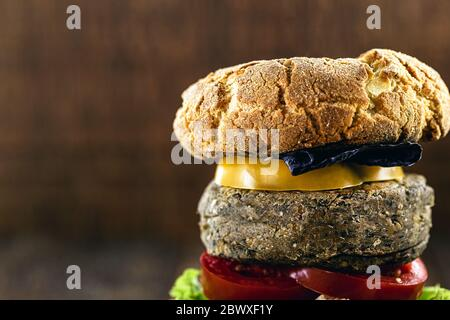 close up on a vegetarian burger, made with vegetables and proteins, such as chickpeas, soybeans, mushrooms, tomatoes, red cabbage, chickens and others - Stock Photo