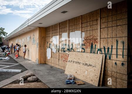 Minneapolis, Minnesota / USA - June 2 2020: Volunteers clean up graffiti on damaged and wrecked building with haunting 'Can you hear us now' graffiti
