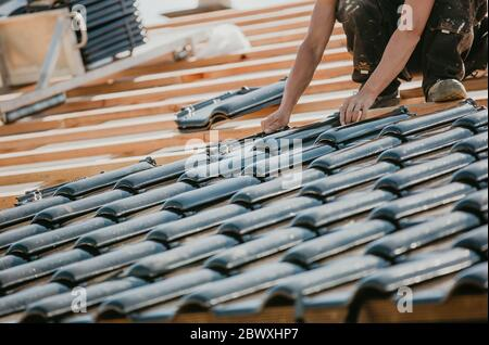 Professional house builder laying roofing or new roof for a new building houses, concept of construction