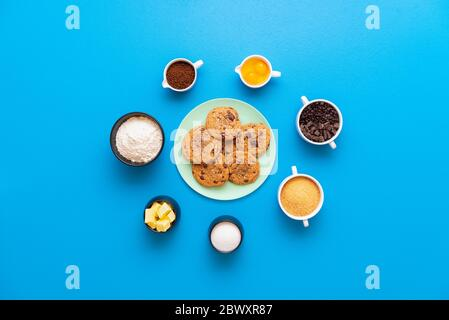 Chocolate chip cookies on a plate and the ingredients for making cookies, on a seamless blue background. Flat lay with recipe ingredients in bowls. - Stock Photo
