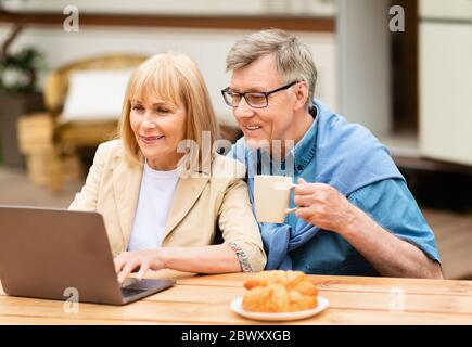Affectionale elderly couple watching video on laptop during vacation in countryside - Stock Photo