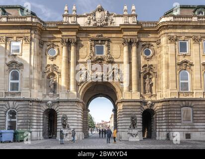 Budapest, Hungary - Feb 9, 2020: Tourists walk towards south side of The Lion's Yard - Stock Photo