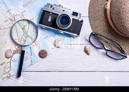 Top view of planning vacation planning using a map, magnifier, retro camera - Travel influencer looking for the next travel destination