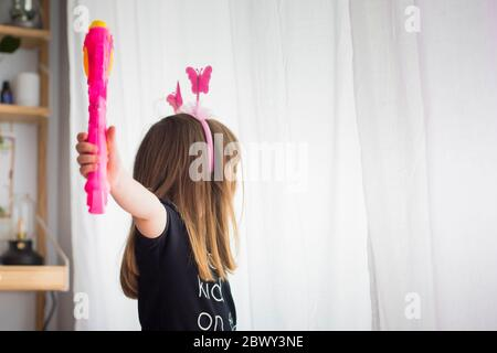 Little child girl, at home playing in disguise wearing  pink antennas and holding a toy magic wand. Gender equality and feminism concept, background.