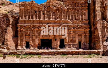 The ornately carved sandstone facade surrounding the entrance of the Palace Tomb in the Royal Tomb complex of Petra - Stock Photo