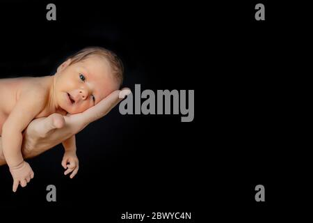 Father holding his 15 days old son in his hand on black background