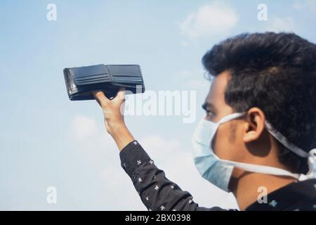 Young man wearing protective face mask and showing his empty wallet on cloud and sky background.selective focus on wallet. - Stock Photo