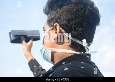 Young man wearing protective face mask and showing his empty wallet on cloud and sky background. - Stock Photo