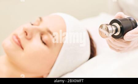 Non injection mesotherapy. Doctor and patient in clinic. Rejuvenation cosmetology tool. Woman aesthetic skin face procedure. Anti wrinkle fr lifting - Stock Photo