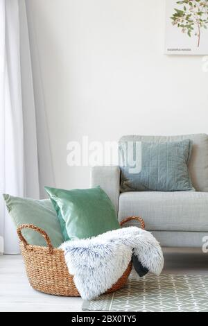 Wicker basket with pillows and plaid near sofa in room - Stock Photo