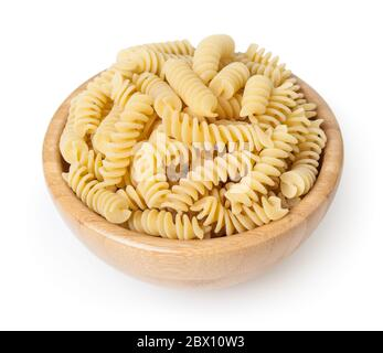 Uncooked fusilli pasta in wooden bowl isolated on white background with clipping path - Stock Photo