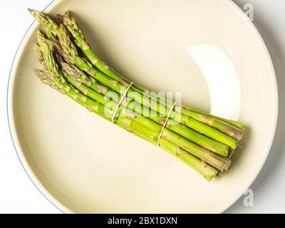 A bunch of asparagus spears in a bowl on a white background - Stock Photo