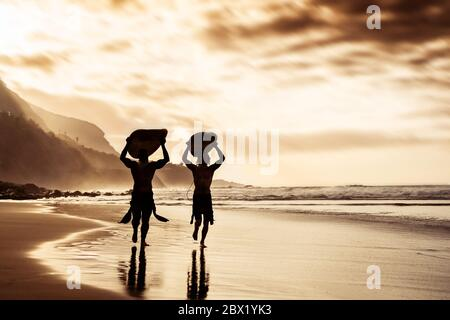 Happy friends running and holding surfboards on beach sunset time - Surfers father and son doing warm up exercise