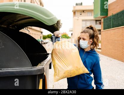 girl throwing the a yellow trash bag into a green recycling container open in the street. The teenager is wearing face mask and gloves to protect hers - Stock Photo