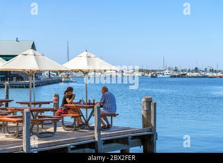Couple sitting at a waterfront cafe / restaurant (Cicerello's), Fremantle Jetty, Fishing Boat Harbour, Fremantle, Western Australia, Australia - Stock Photo