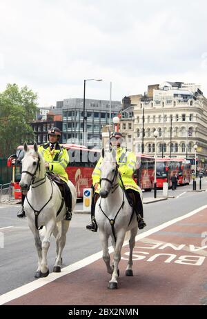 Two British police officers on horseback patrolling the roads of some London streets in the capital city of the United Kingdom - Stock Photo