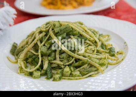 Close up view of a traditional green pasta dish: green Spaghetti with green bean and zucchini, served in a white plate - Stock Photo