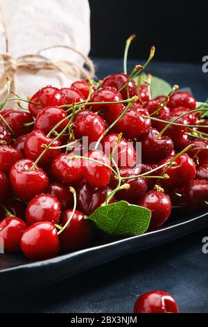 Fresh sweet cherry on a plate on a blue background close-up. Concept of fresh berries, food delivery, eco-friendly packaging. Photo for a grocery