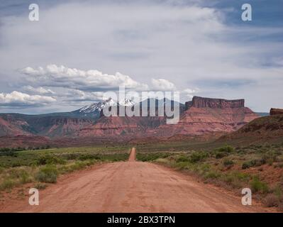 A straight gravel road with beautiful mountain scenery in the background