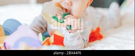 Portrait of a cute 6 month old baby, boy or girl, playing with a teething toy.