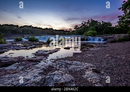 Sunset skies over Grand Falls waterfall in Joplin, Missouri - Stock Photo