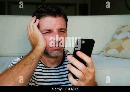 close up face portrait of young attractive and stressed man using mobile phone tired and unhappy in frustrated face expression at home living room in