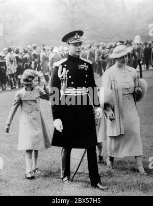 King George VI, Queen Elizabeth, Princess Elizabeth and Princess Margaret Rose ( hidden) on their way to the parade ground for the presentation of the special Coronation Medals for the Dominions and Colonial troops that will be presented at his coronation at Buckingham Palace. Over 1500 soldiers salute the Royal Family.