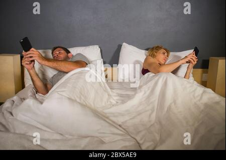 young attractive couple using mobile phone in bed ignoring and neglecting each other obsessed networking in internet addiction and unhappy relationshi - Stock Photo